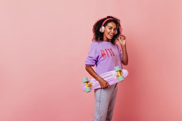 Leuk vrouwelijk zwart model dat paars skateboard houdt. schattige afrikaanse vrouw met krullend kapsel favoriete lied luisteren en glimlachen.