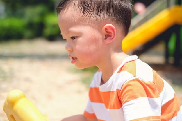 Leuk weinig aziatisch 2 - 3 jaar oud kind die van de peuterjongen tijdens het hebben van pret het spelen zweten, uitoefenen openlucht bij speelplaats, zonnesteekconcept