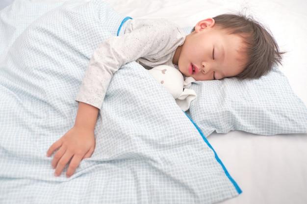 Leuk weinig aziatisch 3 - 4 jaar oud jong geitje van de peuterjongen in pyjama die / een dutje in bed slapen, bedtijd voor jonge geitjesconcept