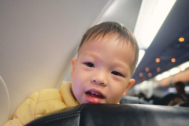 Leuk weinig aziatisch 3 jaar oud de jongenskind dat van de peuterbaby tijdens vlucht op vliegtuig glimlacht