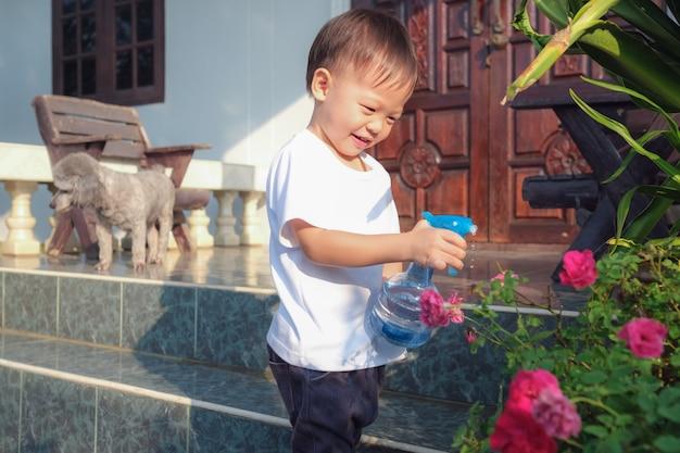 Leuk weinig aziatisch kind dat van de peuterjongen pret heeft die nevelfles met behulp van die roze roze bloemen thuis in zonnige ochtend water geven