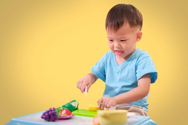 Leuk weinig aziatisch kind dat van de peuterjongen pret het spelen alleen met het koken van speelgoed heeft dat op gekleurde achtergrond met het knippen van weg wordt geïsoleerd