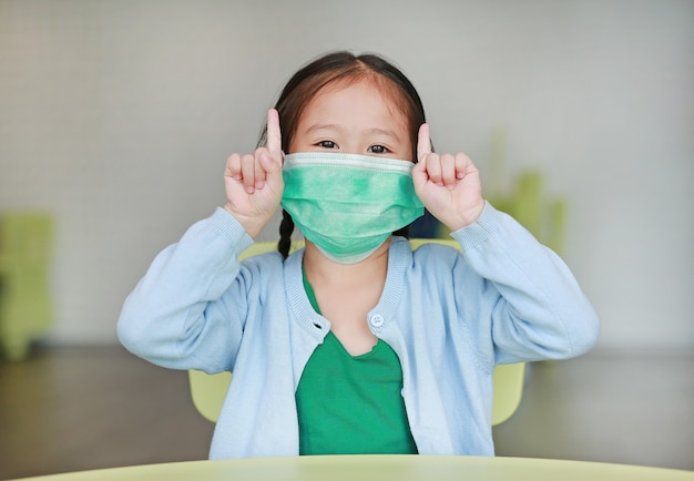 Leuk weinig aziatisch kindmeisje dat een beschermend masker draagt