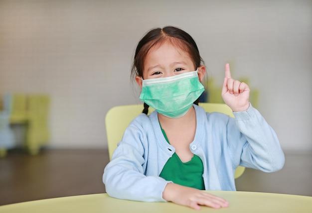 Leuk weinig aziatisch kindmeisje die een beschermend masker met het tonen van één wijsvinger dragen