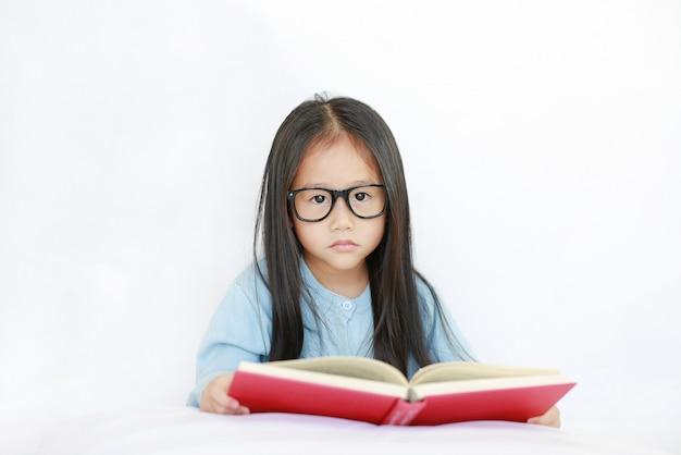 Leuk weinig aziatisch kindmeisje die glazen dragen die hardcover boek lezen die op bed tegen witte achtergrond liggen.
