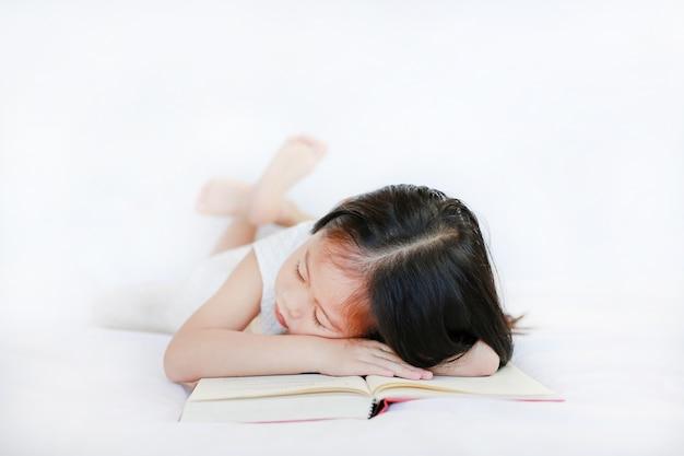 Leuk weinig aziatisch kindmeisje die op hardcoverboek op bed over witte achtergrond liggen.