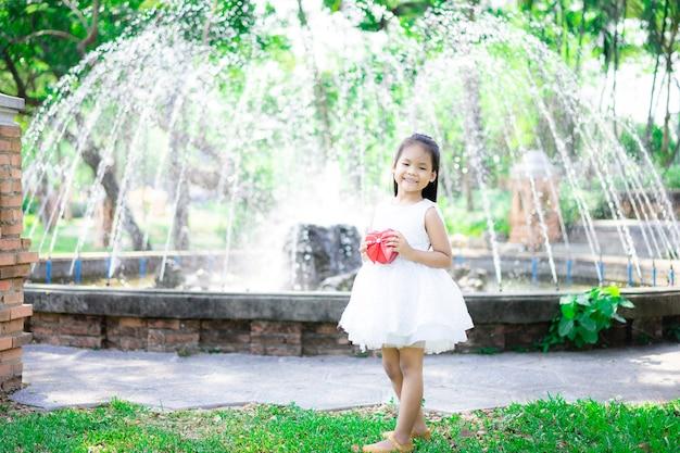 Leuk weinig aziatisch meisje dat in witte kleding een rode gift in het park houdt