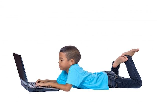 Leuk weinig aziatisch meisjeskind dat op de vloer ligt die of laptop bestudeert gebruikt die op wit wordt geïsoleerd
