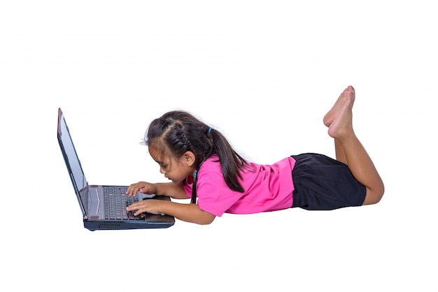 Leuk weinig aziatisch meisjeskind dat op de vloer ligt die of laptop bestudeert gebruikt die op witte achtergrond wordt geïsoleerd