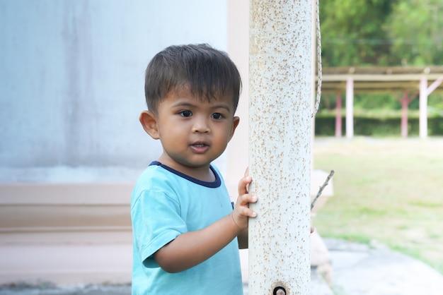 Leuk weinig aziatische jongen die en glimlach bij het park speelt