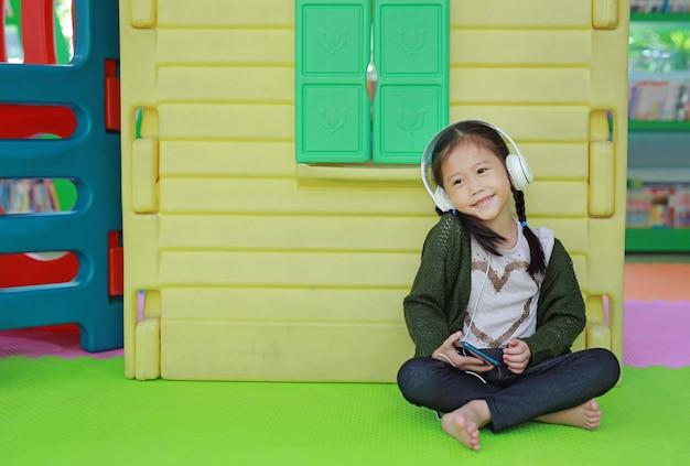 Leuk weinig aziatische kindmeisje het luisteren muziek door hoofdtelefoon dichtbij stuk speelgoed playhouse in speelplaats