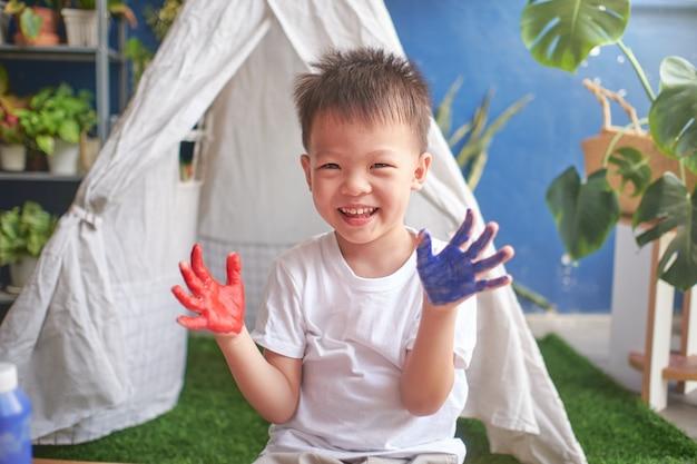 Leuk weinig aziatische vinger die van het jongenskind met handen en waterverven thuis schilderen, creatief spel voor jonge geitjesconcept