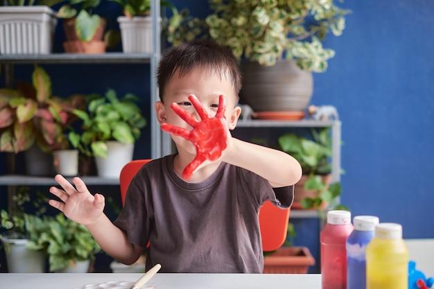 Leuk weinig aziatische vinger die van het jongenskind thuis met handen en waterverf schilderen