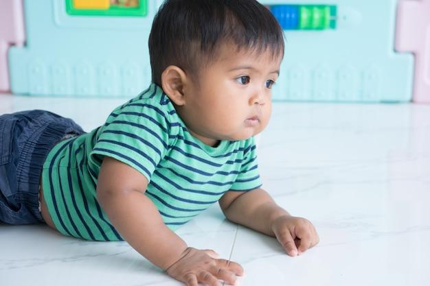 Leuk weinig babyjongen die op vloer kruipen