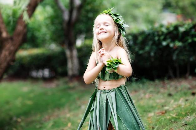 Leuk weinig blondemeisje in carnaval-kostuum dat van groen gras wordt gemaakt openlucht