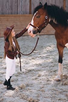 Leuk weinig blondemeisje met paard bij boerderij