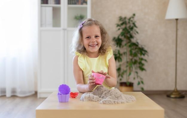 Leuk weinig glimlachend meisje die met kinetisch zand spelen