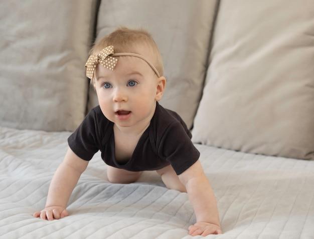 Leuk weinig grappig verbaasd kaukasisch babymeisje met oped mond op bed in zwart lichaam met bruin booglint