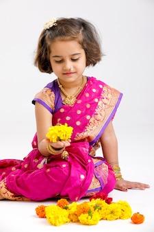 Leuk weinig indisch / aziatisch meisje dat een bloemontwerp maakt
