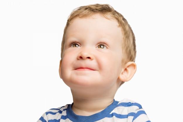 Leuk weinig jongen die, geïsoleerd close-up glimlacht