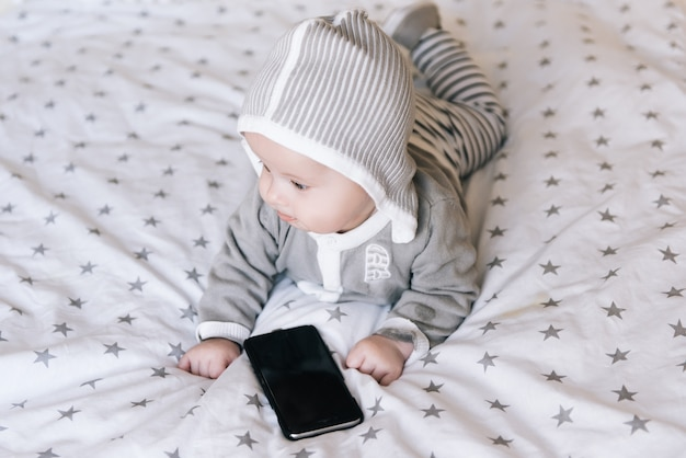 Leuk weinig jongen die op zijn maag ligt en de telefoon, selectieve nadruk onderzoekt