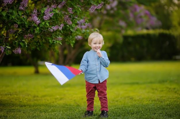 Leuk weinig jongen die russische vlag houdt tijdens het lopen in de zomerpark