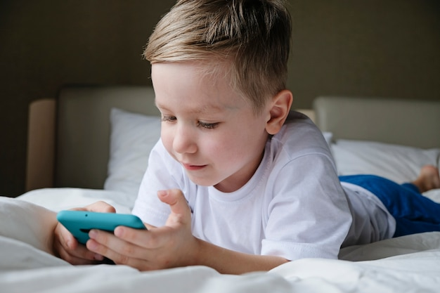 Leuk weinig jongenspeuter die mobiel spel spelen, liggend op een bed en smartphone houden