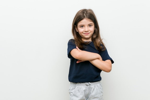 Leuk weinig kaukasisch meisje dat zeker met gekruiste wapens glimlacht.