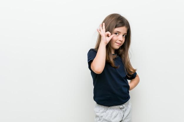 Leuk weinig kaukasisch meisje vrolijk en zeker tonend ok gebaar