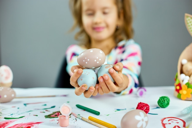 Leuk weinig kindmeisje op paasdag houdt paasei in de hand. meisje met beschilderde eieren op lichte achtergrond, vrolijk pasen