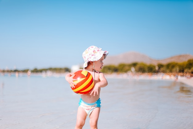 Leuk weinig krullend babyspel met kleurrijke bal op strand. meisje dat op het water bij de kust loopt.