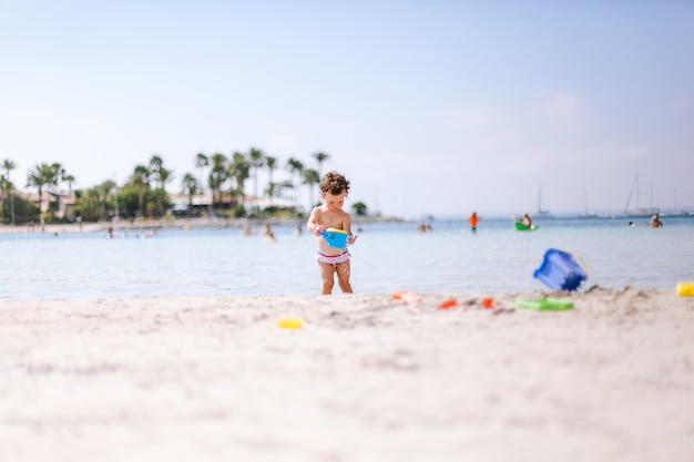 Leuk weinig krullend babyspel met water en zand op strand bij de kust.