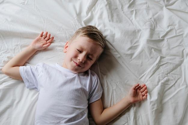 Leuk weinig slaap die van de jongenspeuter op een wit bed in de ochtend liggen