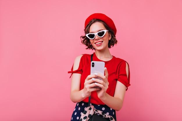 Leuk wit meisje dat in rode baret beeld van zich met glimlach neemt. indoor foto van prachtige kortharige vrouw in zonnebril selfie maken.