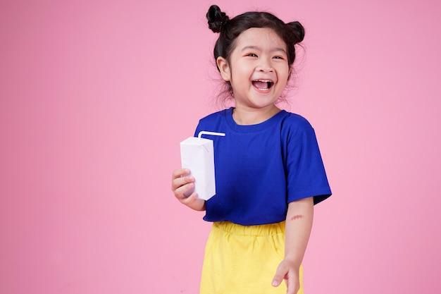 Leuk zelfverzekerd aziatisch klein kindmeisje drinkt melkdoos