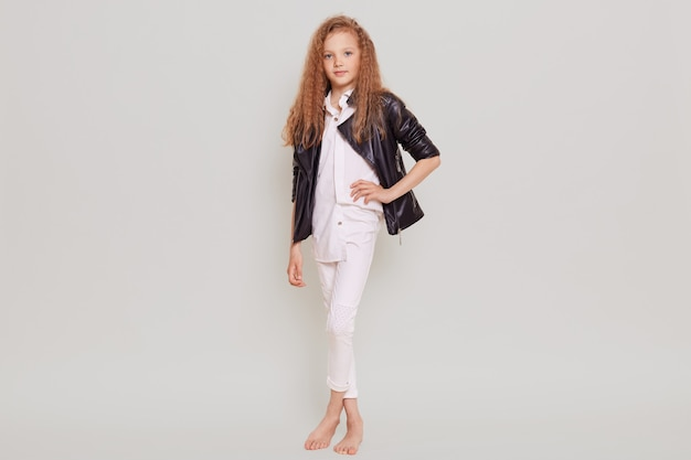 Leuk zelfverzekerd schoolmeisje die witte blouse, broek en leerjasje dragen die zich met hand op heup bevinden, die voorzijde bekijken