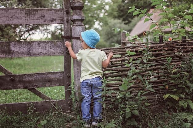 Leuke 4-5 jaar jongen in blauwe hoed die door een oude houten omheining van landhuis tuurt