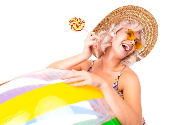 Leuke aantrekkelijke blonde dame in zwembroek en zonnebril houdt een lolly en een zwemmende bal