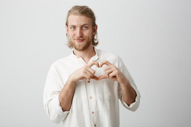 Leuke aantrekkelijke blonde kaukasische kerel met modieuze paardenstaart, baard en snor die gehoord teken tonen en met mooie uitdrukking glimlachen