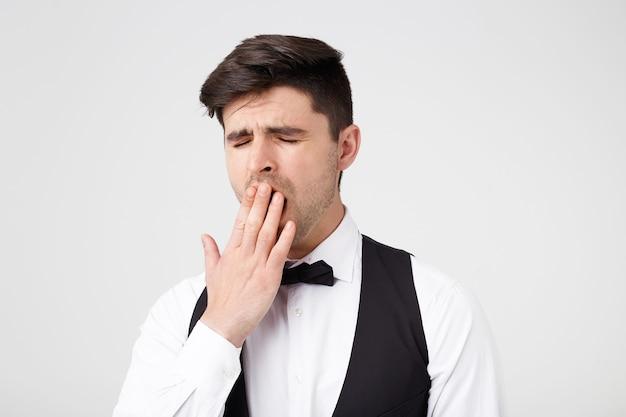Leuke aantrekkelijke brunette man in een pak danste de hele nacht, nu bedekken vermoeide geeuwen zijn mond met zijn hand