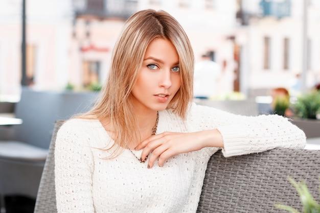 Leuke aantrekkelijke jonge vrouw in een mooie glimlach met blauwe ogen met blond haar in een stijlvolle witte gebreide trui zit op een terras. charmant meisje op vakantie.