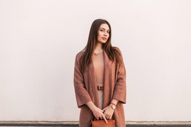 Leuke aantrekkelijke jonge vrouw mannequin in elegante bruine kleding met lederen mode handtas poseren in de buurt van vintage wit gebouw op straat. vrij stedelijk meisje in casual outfit buitenshuis. schoonheidsdame.