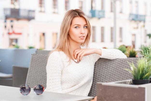 Leuke aantrekkelijke jonge vrouw met blauwe ogen in een stijlvolle gebreide trui zit op een vintage bank op een terras. mooi meisje rusten.