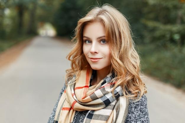Leuke aantrekkelijke mooie jonge vrouw met blauwe ogen met natuurlijke make-up in een stijlvolle jas in een beige vintage sjaal in een kooi staat in het park