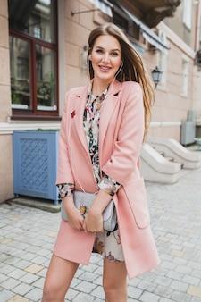 Leuke aantrekkelijke stijlvolle lachende vrouw stad straat lopen in roze jas, luisteren naar muziek op oortelefoons