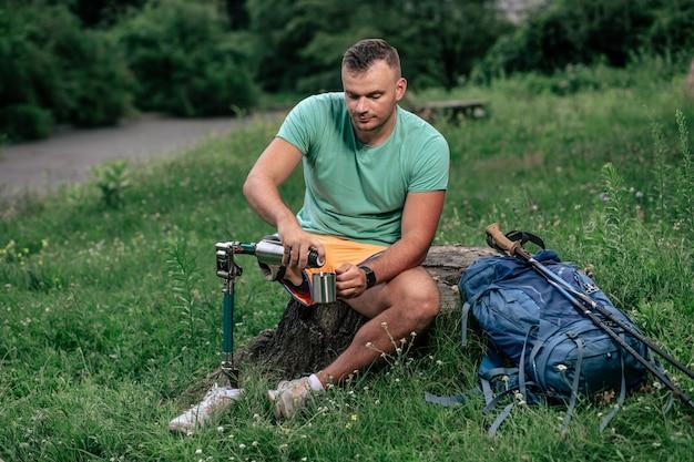 Leuke actieve mannelijke toerist die tee drinkt terwijl hij op de boomstronk rust