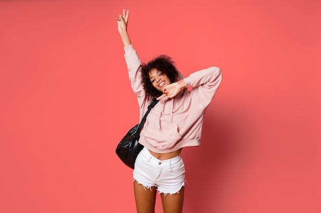 Leuke afrikaanse vrouw die in roze sweatshirt grimassen maken, pret hebben, die over roze achtergrond stellen.