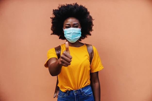 Leuke afrikaanse vrouw permanent buiten met masker op haar gezicht en duimen opdagen. covid19-uitbraak.