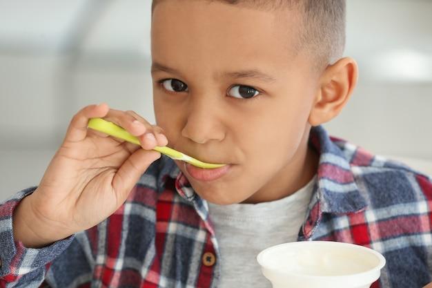 Leuke afro-amerikaanse jongen thuis yoghurt eten, close-up