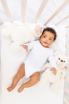 Leuke afro-amerikaanse kleine baby in wit slaapbed met berenspeelgoed.